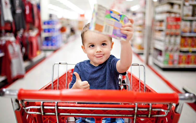 Happy Young Child in Shopping Cart with Toy